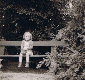 Christin Thauerböck als Kind auf einer Bank vor einem Baum